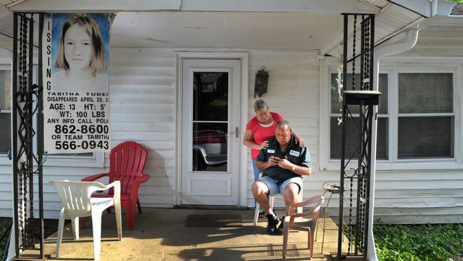 "Bo and Debra Tuders sit on the porch of their East Nashville home last week where the poster of their missing daughter, Tabitha, still hangs out front after 11 years. Tabitha, who was 13, disappeared April 29, 2003. ""She's still out there,"" Bo Tuders said."