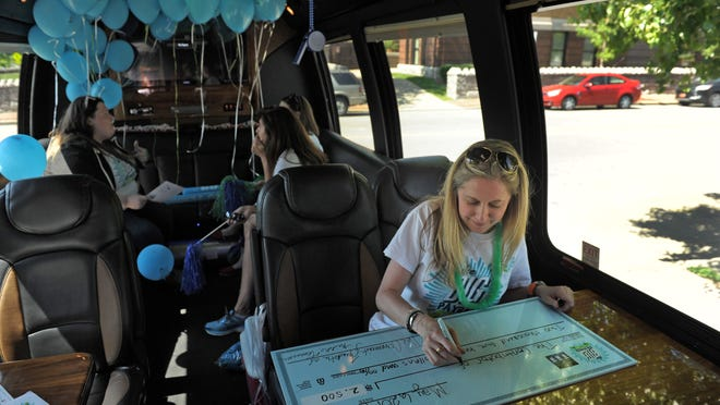 Sarah Sperling of The Community Foundation of Middle Tennessee writes honorary checks with others in The Big Payback party bus in 2014. (File)