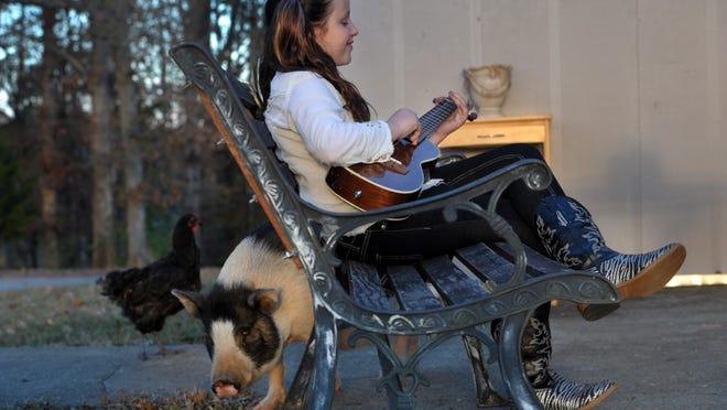 Emi Sunshine Hamilton, 10, strums her mandolin outside with her pet Pig, Pig on Monday Nov. 10, 2014, in Madisonville in Tenn.