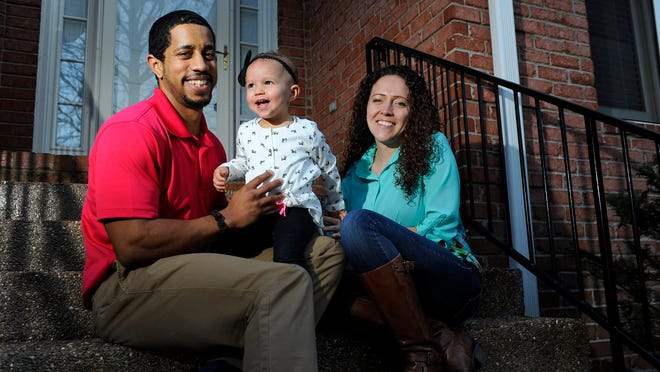 Nigel and Megan LeBlanc cuddle with their daughter Marlee at their home in Donelson. The couple knew they wanted to live and raise their family there and made offers on six other houses before their offer on this one was accepted.