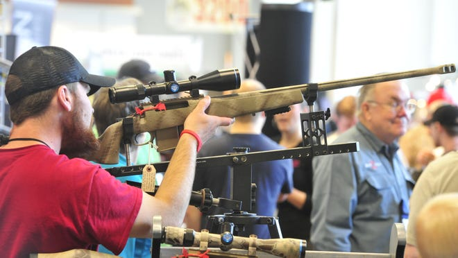 Nathan Kile, of Galveston, Ind., checks out a gun at the NRA convention at the Music City Center in downtown Nashville.