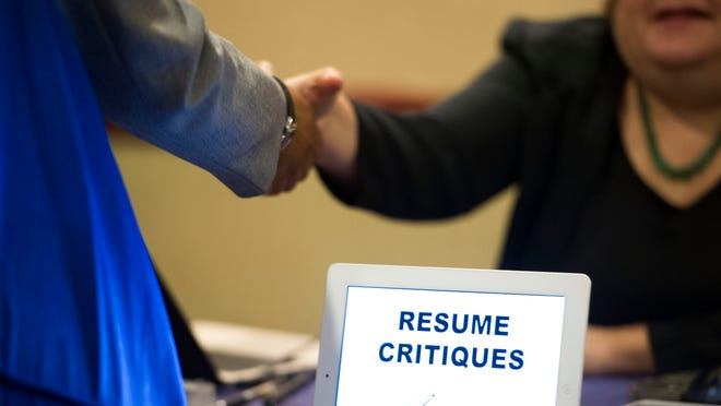 A job seeker stops at a table offering resume critiques during a job fair in Atlanta.