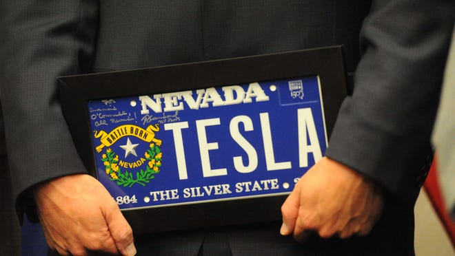 Diarmuid O'Connell Tesla vice president of buiness development, holds a gift from Gov. Brian Sandoval.