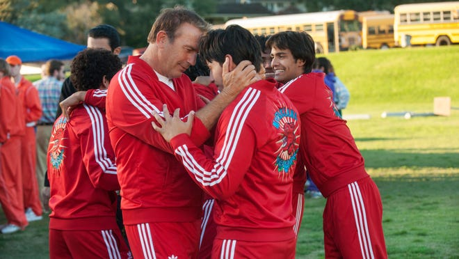 """Kevin Costner (foreground left) embraces Carlos Pratts in a scene from """"McFarland, USA."""""""