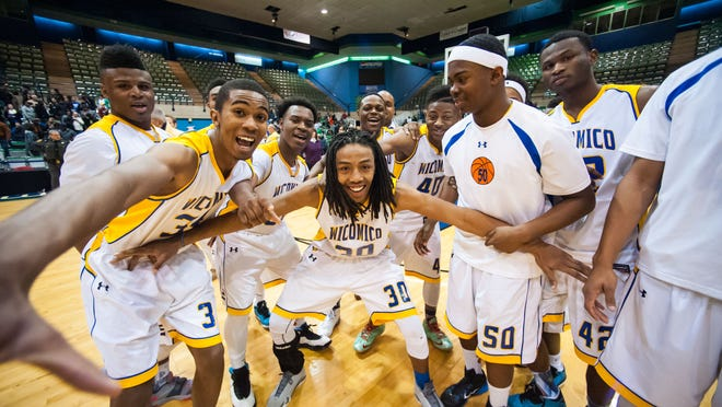 The Wicomico High School boys basketball team celebrates winning the Bayside Championship against Kent County on Wednesday evening at the Wicomico County Youth and Civic Center.