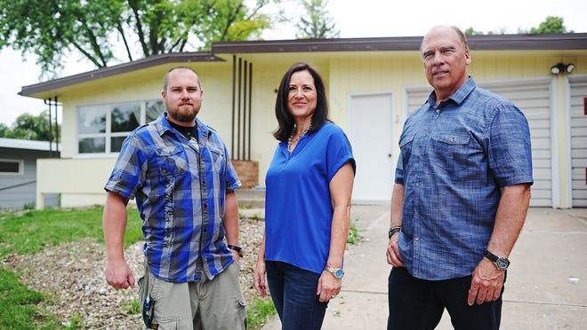 From left, Glenn Stallings, Jane Shorma, of Creative Building Solutions, and Troy Stallings, also of Creative Building Solutions, stand for a group photo on Tuesday, June 17, 2014, in front of Glenn's house, which is in the process of being remodeled, in Sioux Falls, S.D.
