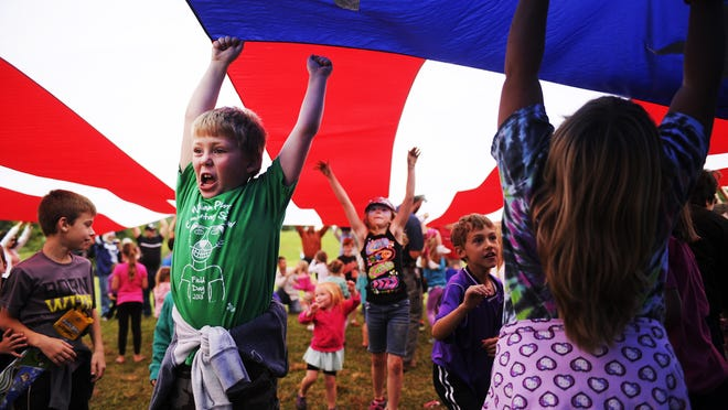 Children play under a large American flag as their parents hold it up at last year's Coyner Springs Kite Fly in Waynesboro.