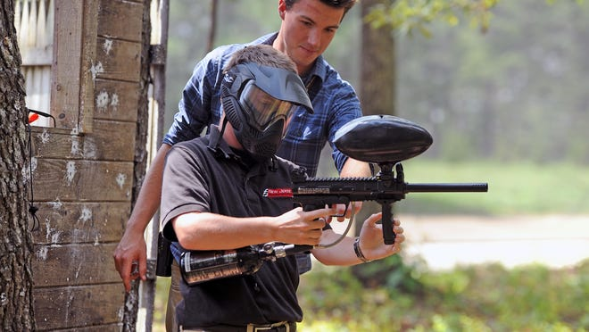 Steve Hahn, manager of the paintball grounds at New Jersey Motorsports Park, shows park spokesman Chris Banker how to handle a paintball gun.