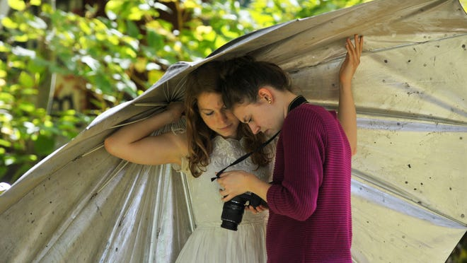 Makayla Slabv, right, and her photographic subject, Verus Juhasz, an exchange student from Hungary, look through their photos in late September during the Visualizing Our Community workshop at a property in Weston owned by local photographer Dave Junion. Junion advised students in their photo quests.
