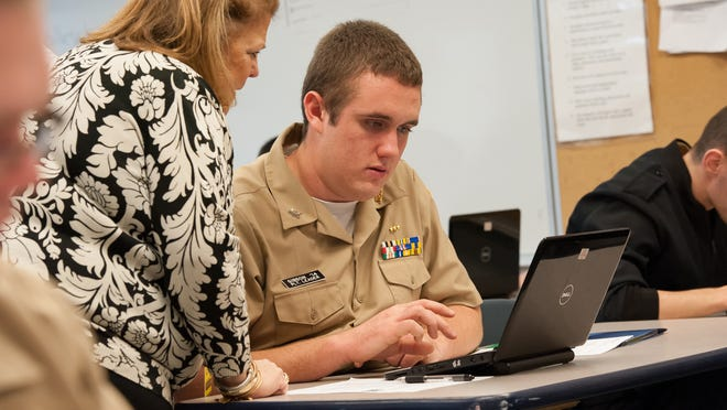 David Gibson, a Delaware Military Academy cadet, worked on his college applications with help from Melinda Girardi, an academic counselor at Delaware Technical Community College. Schools are seeking volunteers to help with the program this year.