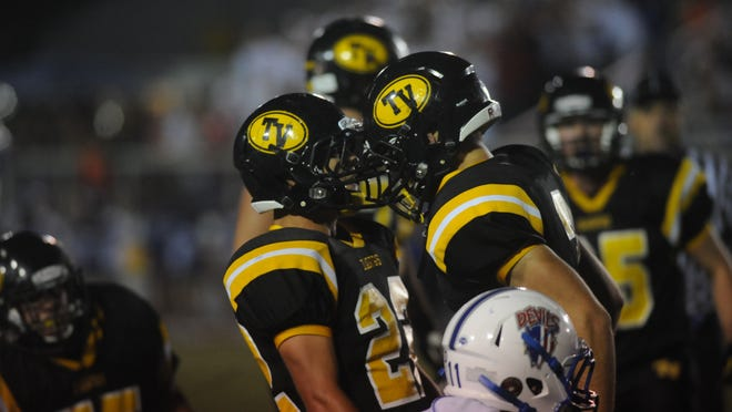 Grant Nolder, right, and Kolton Hanby celebrate a second-quarter sack during Tri-Valley's 35-0 win against Zanesville at Jack Anderson Stadium. Nolder had three sacks in the game.