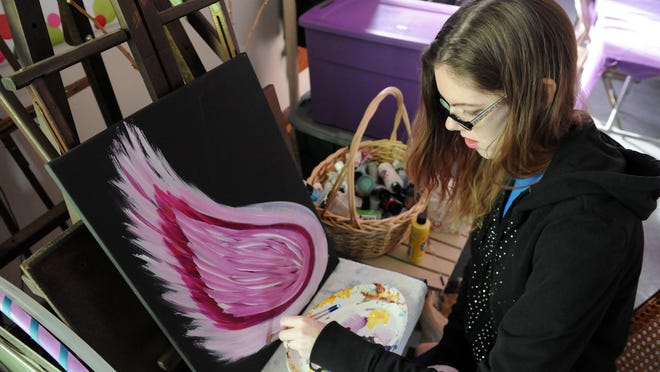 Artist Carrie Turner works on an original painting Dec. 7 at the Artist Collective inside the Masonic Temple in Zanesville.