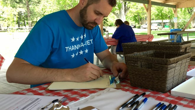 St. Thomas Church Pastor Josh Miller writes a letter for Operation Gratitude, a national nonprofit that sends 150,000 care packages annually to service members, veterans and their caregivers, on May 29 in City Park. He took part in a thank-a-veteran event organized by St. Thomas Church.