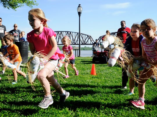 "Participants dash out of the starting gate for the stick horse race at  ""Run for the Roses"" last year."
