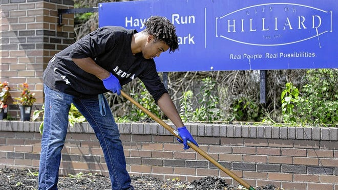 Redwan Kamel, 18, of Hilliard rakes Aug. 15 after pulling out weeds that surround the Hayden Run Village Park sign on the corner of Avery and Davidson roads. Since he was a Boy Scout in the sixth grade, Kamel has done his part to keep the park clean and manicured.