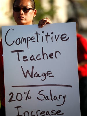 "A teacher at Tuscano Elementary School joins dozens of teachers, parents and students as they stage a ""walk-in"" for higher pay and school funding on April 11, 2018, in Phoenix. Teachers gathered outside Arizona schools to show solidarity in their demand for higher salaries staging ""walk-ins"" at approximately 1,000 schools that are part of a statewide campaign for a 20 percent raise and more than $1 billion in new education funding."