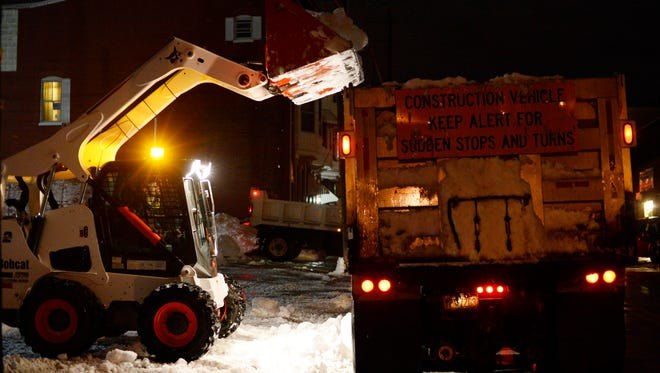 Crews use a bobcat and dump truck for snow removal of a lot on South Pershing Avenue in York Tuesday, January 26, 2015. Crews continue to work 12-hour shifts around the clock dealing with the approximately 30 inches of snow that blanketed the city last weekend.