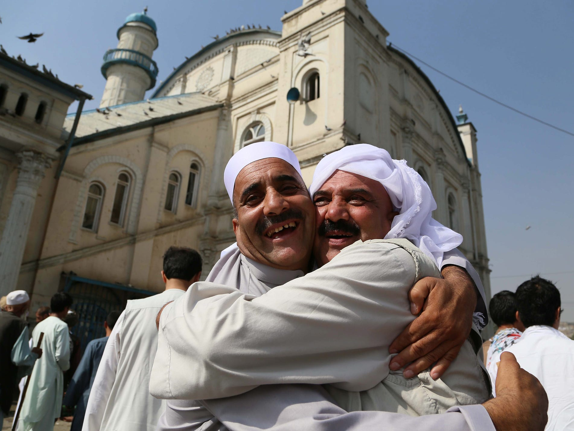 Men greet each other after offering prayers during the Eid al-Fitr celebration on Aug. 8 in Kabul, Afghanistan. Muslims around the world began celebrating the three-day festival of  Eid al-Fitr, which marks the end of the holy fasting month of Ramadan.