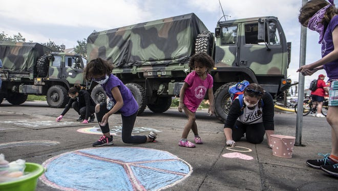 Children write encouraging messages on the sidewalk in Minneapolis on May 30,  following a night of unrest and protests over the killing of George Floyd.