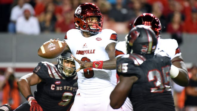 Oct 5, 2017; Raleigh, NC, USA; Louisville Cardinals quarterback Lamar Jackson (8) looks to pass as North Carolina State Wolfpack defensive end Bradley Chubb (9) pressures during the first half at Carter-Finley Stadium. Mandatory Credit: Rob Kinnan-USA TODAY Sports
