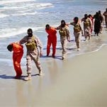 This undated image made from a video released by Islamic State militants, Sunday, April 19, 2015, appears to show a group of captured Ethiopian Christians in Libya.  The 29-minute video released online Sunday purportedly shows two groups of captives. It says one group is held by an IS affiliate in eastern Libya and the other by an affiliate in the south. A masked fighter delivers a long statement before the video switches between footage that purportedly shows the captives in the south being shot dead and the captives in the east being beheaded on a beach.