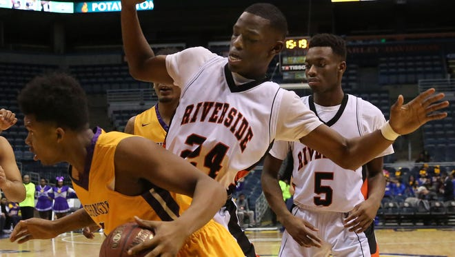 Washington's Deontay Long looks for an outlet as he is boxed in by Riverside's Terrance Lewis.