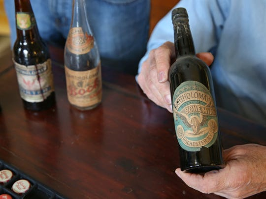 John DeVolder holds a Bartholomay Brewing Company of Rochester, NY beer bottle, part of his and his son Jim DeVolder's collection of beer memorabilia in John's home in Ontario, Wayne County, Wednesday, Jan. 10, 2018.