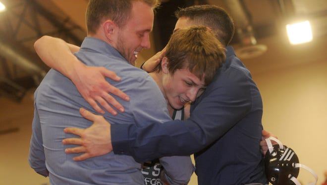 "West Deptford's Dylan Fischer hugs head coach Christian Scannell, left, and assistant Anthony Rizzolo, right, after pinning Clearview's Brandon Dick in a 126-pound championship bout during the District 29 Tournament on Saturday. ""I didn't expect to like Scannell,"" Fischer said Sunday. ""But he's a father figure to me now. I look up to him"""