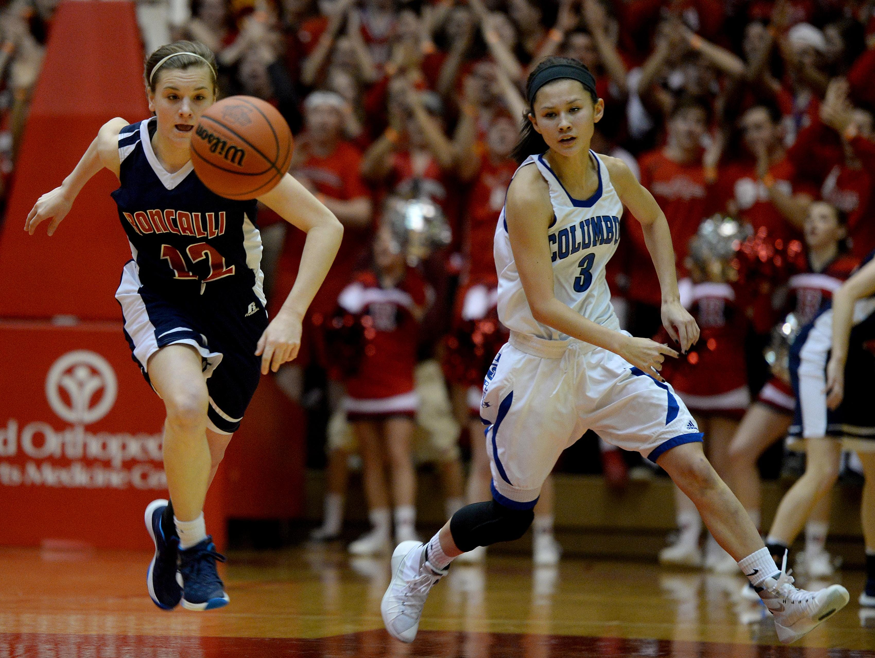 Roncalli's Paige Saylor, left, and Columbus North's Emily Kim chase down a loose ball during the IHSSA girls basketball class 4A semistate game Saturday at the Tiernan Center in Richmond High School.