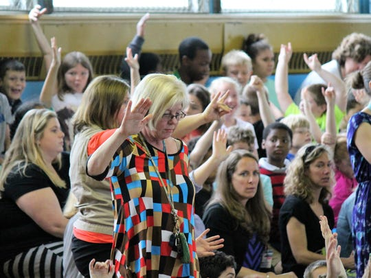 Teachers hold their hands up to quiet the students