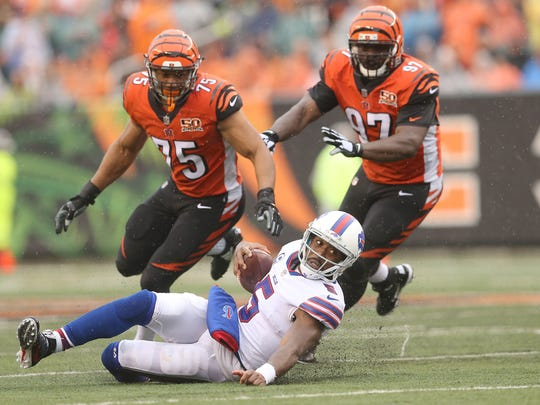 Buffalo Bills quarterback Tyrod Taylor (5) slides down after pressure from Cincinnati Bengals defensive end Jordan Willis (75), left, and Cincinnati Bengals defensive tackle Geno Atkins (97), right, in the third quarter during the Week 5 NFL game between the Buffalo Bills and the Cincinnati Bengals, Sunday, Oct. 8, 2017, at Paul Brown Stadium in CIncinnati.