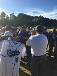 Tracy Westfall, mother of Tucker Westfall, hugs player Dakota Willemssen after the Athens baseball earned a state tournament trip at the White Lake Sectional on Tuesday. Tucker Westfall died in a UTV crash Saturday. His No. 12 jersey is in the foreground.