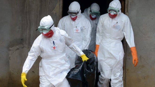 Medical workers of the Liberian Red Cross, wearing a protective suit, carry the body of a victim of the Ebola virus in a bag on September 4, 2014 in the small city of Banjol, 30 kilometres of Monrovia. More than 1,900 people have died in the Ebola epidemic sweeping through West Africa, the head of the World Health Organization said on September 3.