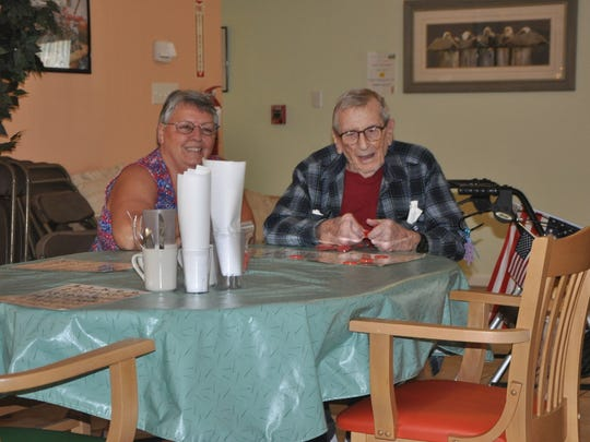 Diane Freese chats with 96-year-old Pelican Garden resident, Jack, as he manages a three-card Bingo round.