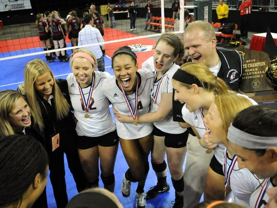 Menomonee Falls players Katherine VonBank (12), Simone Lee, Abby Becker and Lyndsey Bassler, right center, react with their coach J.C. Bruns after their victory over Westosha Central during the Division 1 WIAA Girls State Volleyball Championship at the Resch Center in Green Bay, Wis., on Saturday, Nov. 9, 2013. Photo by Corey Wilson