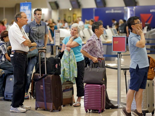 Delta passengers stand in line as the carrier slogged
