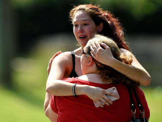 Kaitlyn Adams, a member of the church, hugs another