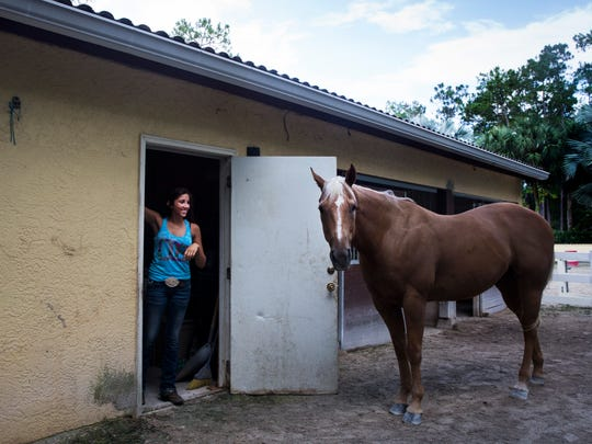 Rachel Caprio,18, laughs at her horse Frenchmans Honor as she puts her riding gear away at her home in Naples on Friday, July 21, 2017.