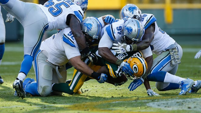 Packers WR Randall Cobb is tackled by the Lions in the fourth quarter at Lambeau Field on Sunday.