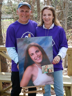 Mike and Kim Roderick hold a photo of their daughter, Courtney, and a smaller photo of Courtney's three children, at their home in Tiverton in 2019.