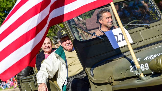 World War II veteran and owner of Noah's Ark, Noah Lacona (center), rides in the parade on Saturday, September 19, 2015, during the Beaverdale Fall Fest parade.