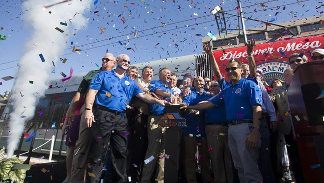 Dignitaries set off confetti during the Central Mesa light rail extension opening celebration on Saturday, August 22, 2015.