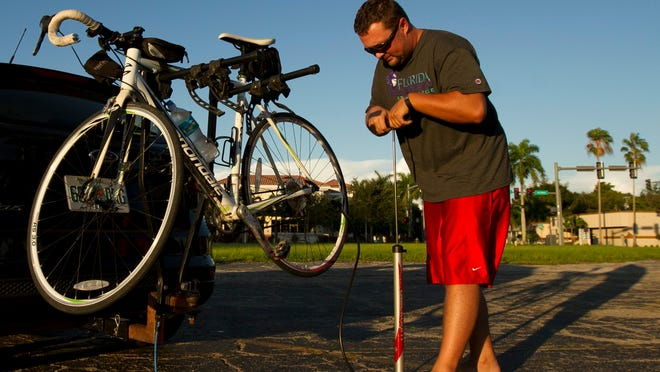Fort Myers resident Dan Kroeker pumps up his bicycle tire in Fort Myers on Friday evening, Oct. 3, before going on a ride with a riding group, SWFL Critical Masse.