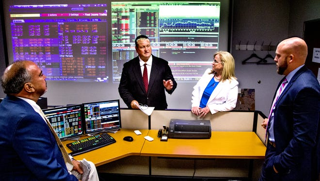 Senior portfolio manager Timothy White (left), chief investment officer and portfolio manager Patricia Humbert and investment analyst Jake Richardson, investment analyst meet in the trading room of the Arizona State Treasurer's Office on June 21, 2016.