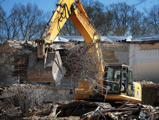 A demolition specialist clears away debris from the