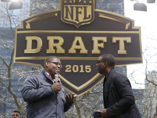 Cris Carter, right, interviews Duke's Laken Tomlinson, during introductions at a pre-draft rally of 2015 NFL Draft prospects, and various league legends at Pioneer Court, Wednesday in Chicago.