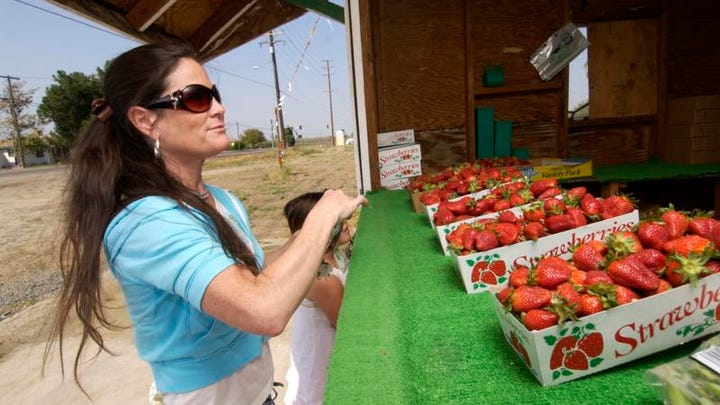 Kim Felsted, left, can't wait to purchase fresh strawberries at Caldwell Avenue and Ben Maddox Way in Visalia. Also pictured is her daughter Olivia. Fresh locally picked strawberry stands open around town, this one is at Caldwell Ave and Ben Maddox Way.