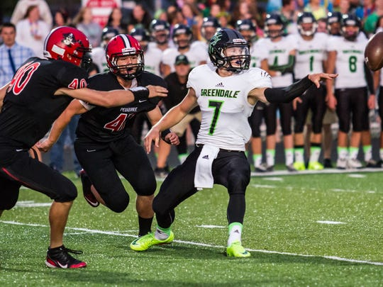 Greendale quarterback Josh Ringelberg (7) flips a lateral to his running back with Pewaukee defenders closing in during a game in 2014. Ringelberg was a two-time All-Suburban Player of the Year recipient.