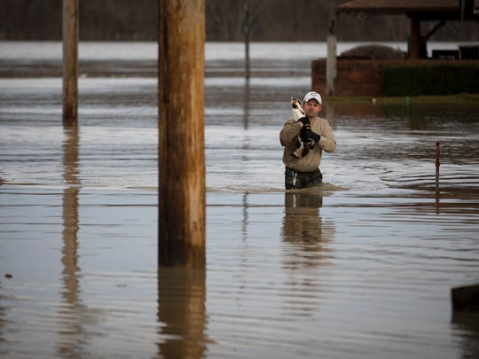 "Sun., Feb. 25, 2018: Chad Koller carries his cat, Livy, on Sunday afternoon, after the Ohio River flooded his Aurora, Indiana apartment. Saturday morning, he ""woke up into it Ð waist-high water,"" he said. Koller lost his phone and his water in the flood the day before and came back Sunday to rescue his two cats. ""I couldn't find her. I was hoping she was still alive. Then she poked her head out of cabinet,"" he said. He still hadn't found his other cat. This has been the most significant Ohio River flooding since 1997. The Enquirer/Carrie Cochran"