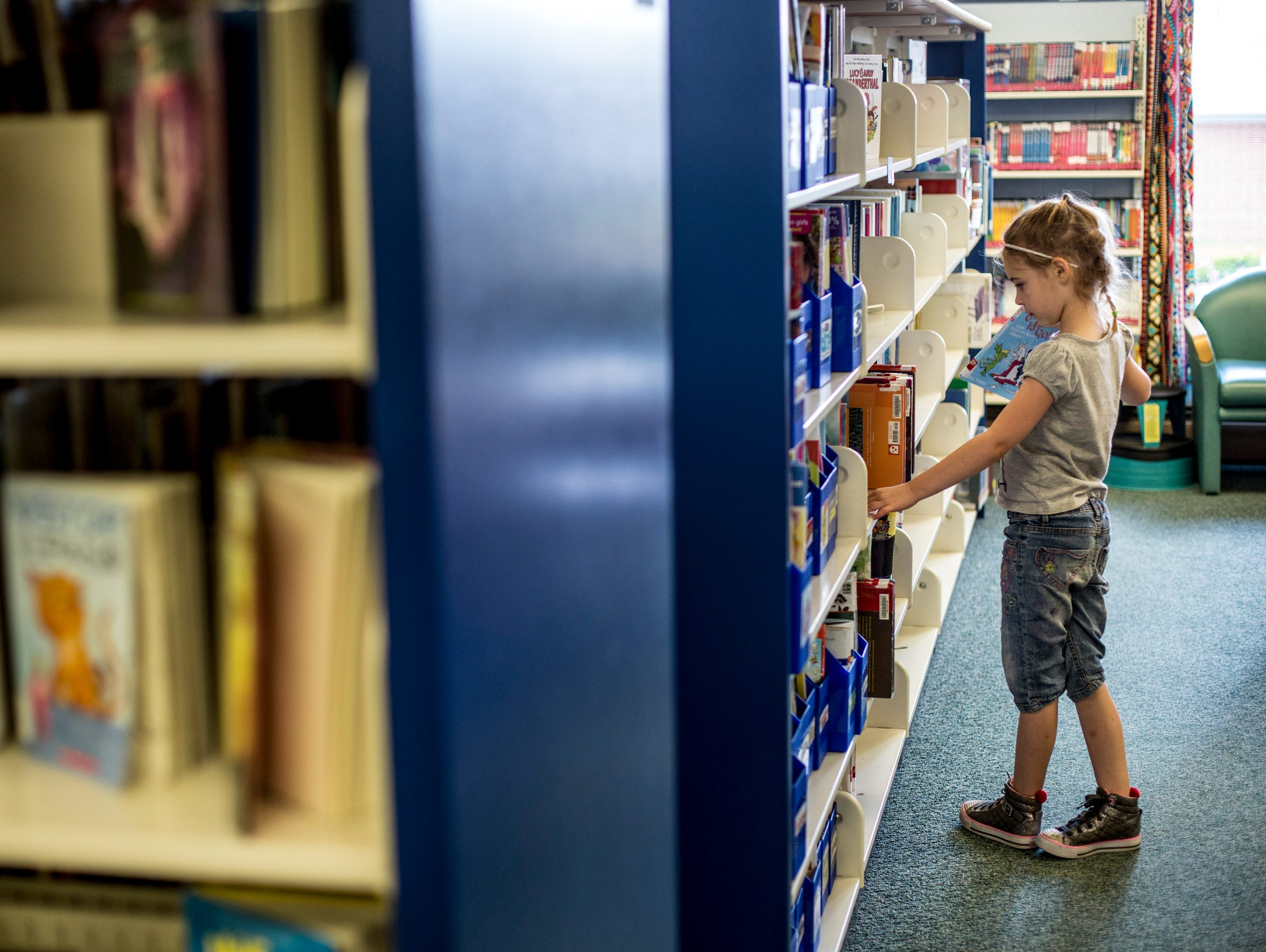Tori Stein, 8, looks over book shelves during one of